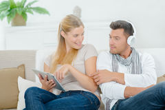 Couple relaxing on sofa with gadgets Stock Photo