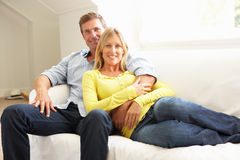Couple Relaxing On Sofa At Home Royalty Free Stock Image