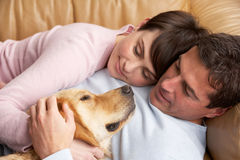 Couple Relaxing On Sofa At Home Stock Photos