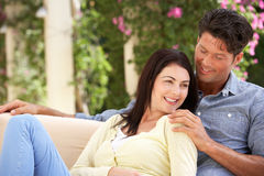 Couple Relaxing On Sofa At Home Stock Image