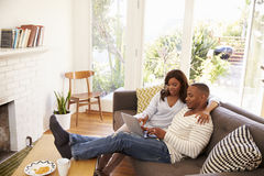Couple Relaxing On Sofa At Home Using Laptop Royalty Free Stock Photography