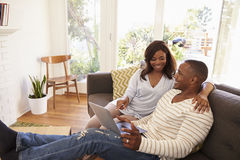 Couple Relaxing On Sofa At Home Using Laptop Stock Photos