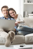 Couple relaxing on sofa with laptop Stock Photos