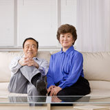 Couple relaxing on sofa in livingroom Stock Photos