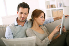 Couple relaxing in sofa stock images