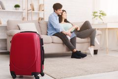 Couple relaxing on sofa with suitcase on foreground. Travel concept. Couple relaxing on sofa with suitcase on foreground royalty free stock image