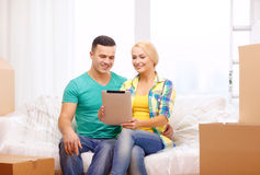 Couple relaxing on sofa with tablet pc in new home Stock Images