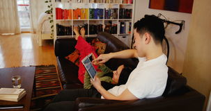 Couple relaxing on sofa using digital tablet and mobile phone in living room. At home stock video footage