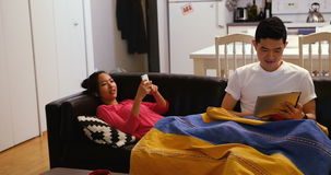 Couple relaxing on sofa using digital tablet and mobile phone in living room. At home stock video