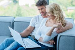 Couple relaxing on a sofa using laptop Stock Photo