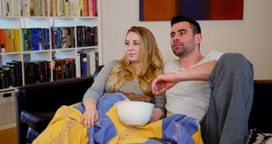 Couple relaxing on sofa watching tv in living room stock footage