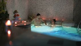 Couple relaxing and speaking together in a sauna at the hotel spa stock video footage