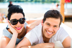 Couple relaxing in summer sun on beach Royalty Free Stock Photos