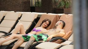 Couple relaxing on sun loungers near the swimming pool stock video footage