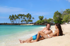 Couple relaxing on suntan beach vacation holiday. Couple relaxing on suntan beach vacation relaxation holiday. Happy young adults sunbathing together tanning stock photo
