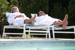 Couple relaxing by swimming pool Royalty Free Stock Photography