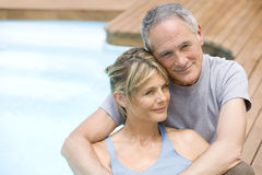Couple Relaxing By Swimming Pool Stock Photo
