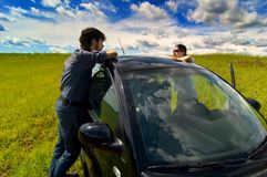 A Couple Relaxing By Their Car. In an empty field Royalty Free Stock Images