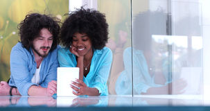 Couple relaxing together at home with tablet computer. Happy young multiethnic couple lying on floor having fun using Digital Tablet Stock Photography