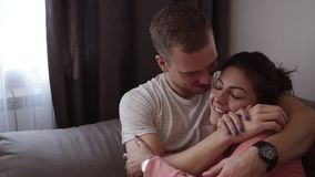 Couple relaxing together on sofa. Romantic young happy couple lying at home in sofa resting having fun together, playing. Loft interior room stock video footage