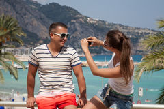 Couple relaxing. Travel women using smartphone to take a husband photo in Promenade, Menton - town and touristic resort on French Riviera. Travel couple having stock photos