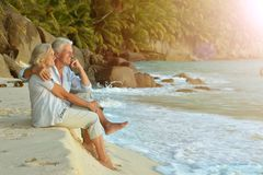 Couple  relaxing on  tropical beach. Happy elderly couple  relaxing on  tropical beach Royalty Free Stock Photos