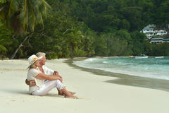 Couple  relaxing on  tropical beach. Happy elderly couple  relaxing on  tropical beach Royalty Free Stock Image