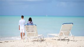 Happy couple relaxing on a tropical beach. Family of two walking together on caribbean holidays. Couple relaxing on a tropical beach at Maldives stock video