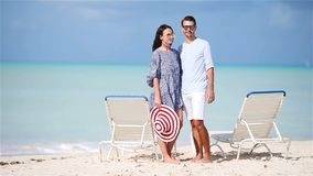 Happy couple relaxing on a tropical beach on sunbed. Couple relaxing on a tropical beach at Maldives stock video