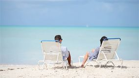 Happy couple relaxing on a tropical beach on sunbed. Couple relaxing on a tropical beach at Maldives stock footage