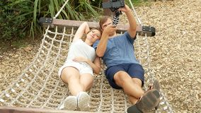 Couple relaxing in a tropical hammock in a city amusement park. do selfie on the camera. 4k. space for copying.  stock video footage