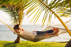 Couple relaxing in tropical hammock Royalty Free Stock Image