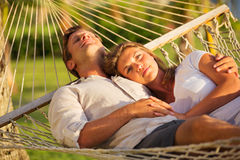 Couple relaxing in tropical hammock Stock Photography