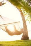 Couple relaxing in tropical hammock Stock Photos