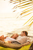Couple relaxing in tropical hammock Royalty Free Stock Photos