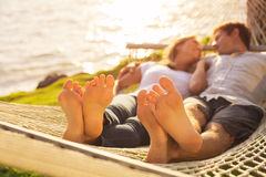Couple relaxing in tropical hammock Stock Images