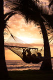 Couple relaxing in tropical hammock Stock Image