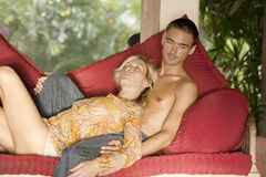 Couple Relaxing on Vacations. Young couple relaxing on a red sofa while on vacation Stock Image