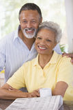 Couple Relaxing With A Newspaper Smiling Stock Image