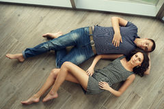 Couple relaxing on wooden floor Stock Photos