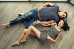 Couple relaxing on wooden floor Stock Photography