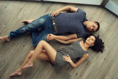 Couple relaxing on wooden floor Royalty Free Stock Image