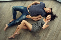 Couple relaxing on wooden floor Royalty Free Stock Photo