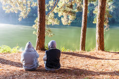 Couple relaxing with worm sunlight in the cold morning near lake Royalty Free Stock Photo