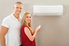 Couple with remote control air conditioner Royalty Free Stock Image