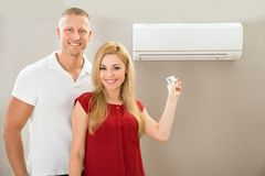 Couple with remote control air conditioner stock photo