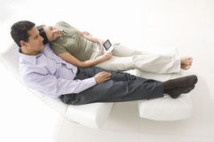 Couple With Remote Control Relaxing On Chair stock image