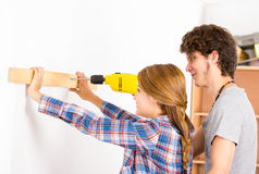 Couple renovating together as man using power Royalty Free Stock Image