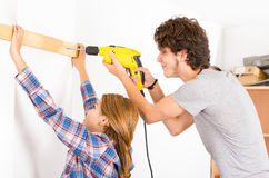 Couple renovating together as man using power. Couple renovating together as men using power drill on wood part and women helping out by holding Royalty Free Stock Photos