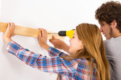 Couple renovating together as man using power Stock Images